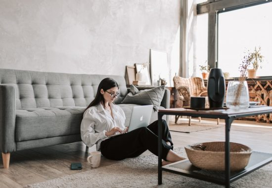 woman sitting on the floor while using her laptop