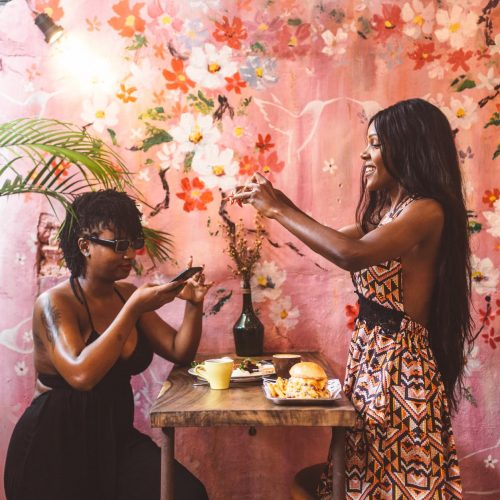 cheerful black women taking pictures on food on smartphone